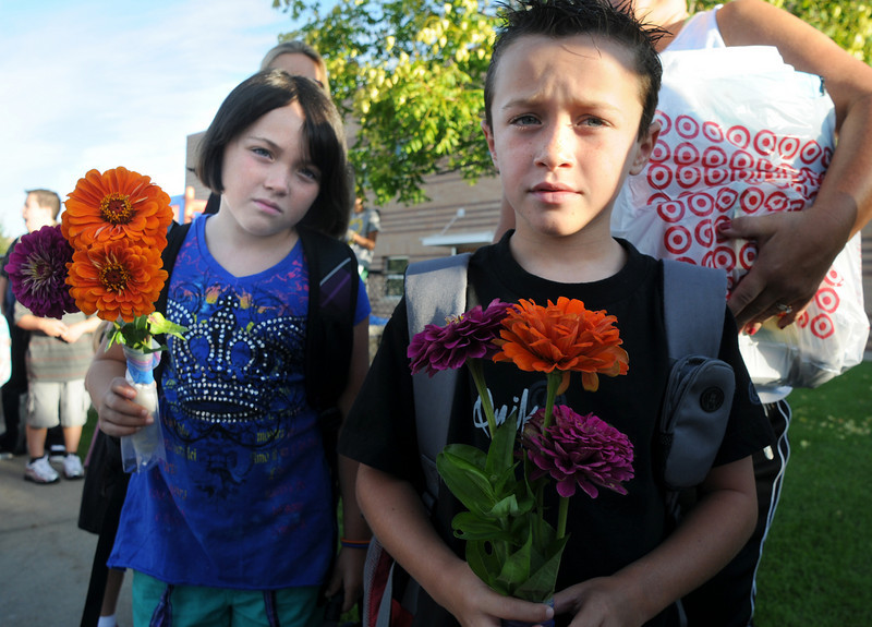 Kade Carlile, 6, right, and his sisiter Kalysta, 8, hold flowers for their teacher on the first day of school at Coyote Ridge Elementary School on Wednesday.<br /> August 18, 2010<br /> staff photo/David R. Jennings