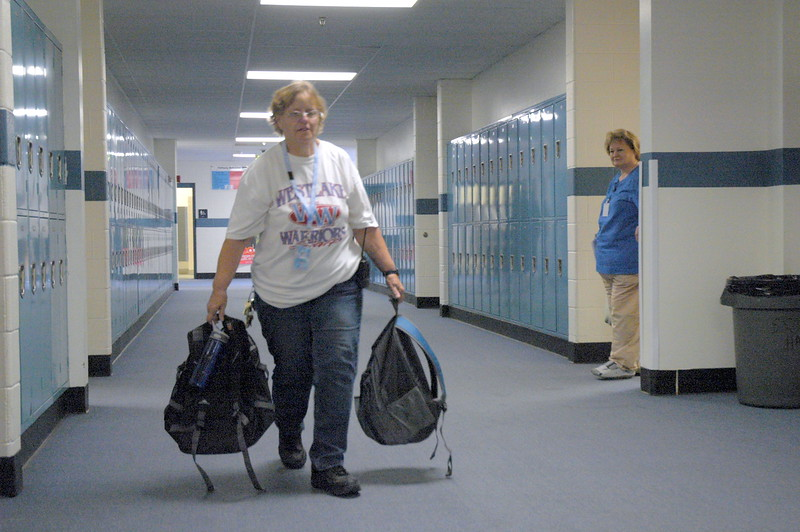 Custodian Loletta Gilchrest carries two backpacks left in the hallway to lost and found at Westlake Middle School's freshman orientation 08/18/10. By Dylan Otto Krider