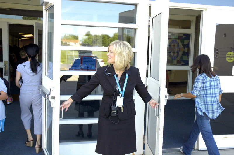 Principal Jessica Fiedler holds the doors open for students entering Westlake Middle School's freshman orientation 08/18/10. By Dylan Otto Krider