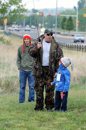 Instructor John Jeffery, center, gives casting pointers to Landon Gunderson, 6, left, with his father Scott during Saturday's Fishing Derby at Tom Frost Reservoir.<br /> May 12, 2012 <br /> staff photo/ David R. Jennings