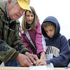 Juan Presas, left, helps Miles Ward, 8, and his mother Jamilyn how to tie the proper fishing knots during Saturday's Fishing Derby at Tom Frost Reservoir.<br /> May 12, 2012 <br /> staff photo/ David R. Jennings