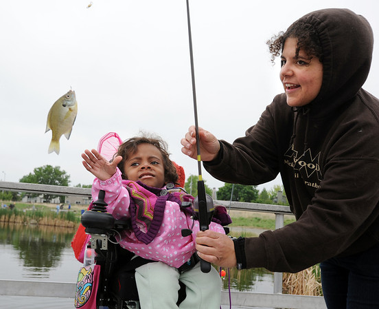 Anicee Lamoreaux, 8, left, reaches to touch the fish she caught being held by her aunt, Stacey Hunvald, during Saturday's Fishing Derby at Tom Frost Reservoir.<br /> <br /> May 10, 2012 <br /> staff photo/ David R. Jennings