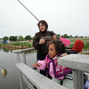 Anicee Lamoreaux, 8, right, has help from her aunt, Stacey Hunvald, with bringing in a fish she caught from the dock at Tom Frost Reservoir during Saturday's Fishing Derby.<br /> <br /> May 10, 2012 <br /> staff photo/ David R. Jennings