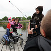 Anicee Lamoreaux, 8, left, poses fro a picture by her father, Chris Lamoreaux, right, with her aunt, Stacey Hunvald, after catching a fish  during Saturday's Fishing Derby at Tom Frost Reservoir.<br /> <br /> May 10, 2012 <br /> staff photo/ David R. Jennings