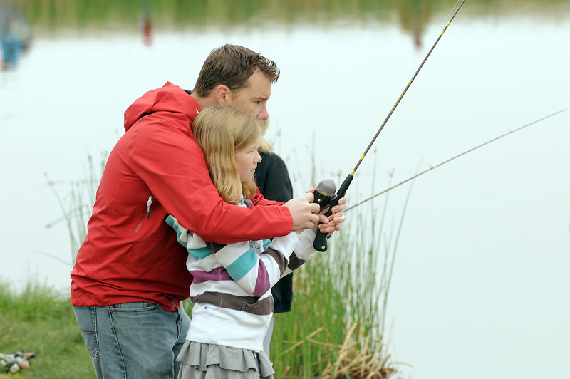MaKenna Hardy, 10, gets some help from her father Doug with bringing in a fish she caught during Saturday's Fishing Derby at Tom Frost Reservoir.<br /> May 12, 2012 <br /> staff photo/ David R. Jennings