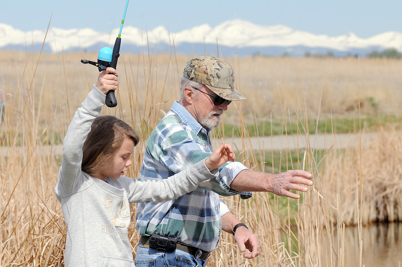 Emmy Hoeben, 9, with her grand father Wayne Hoeben reach for the fishing line during Saturday's fishing derby at Tom Frost Reservoir  sponsored by the Broomfield Open Space Foundation in cooperation with the Colorado Division of Wildlife and the City and County of Broomfield.<br /> May 7, 2011<br /> staff photo/David R. Jennings