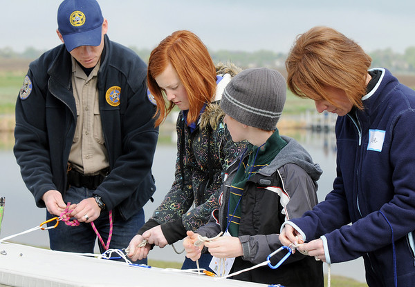 Colorado Division of Wildlife Officer Jason Duetsch, left, demonstrates how to tie a knot to Sarah Howell, 12, her brother Brad, 10, and their mother Julie Weaver during the Fishing Derby sponsored by the Colorado Division of Wildlife and Broomfield Open Space Foundation at Tom Frost Reservoir on Saturday.<br /> May 14, 2010<br /> Staff photo/ David R. Jennings