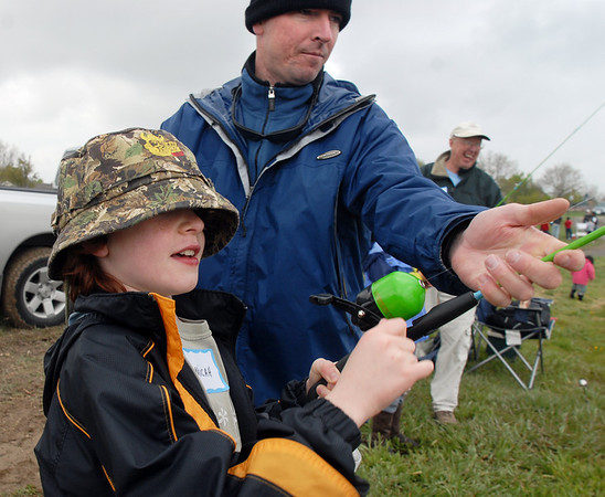 """Micah Oren, 9, left, reels in the first catch of the day with the help of his father Bret during the Fishing Derby sponsored by the Colorado Division of Wildlife and Broomfield Open Space Foundation at Tom Frost Reservoir on Saturday. Micah Oren nicknamed the fish """" Big Willy"""".<br /> May 14, 2010<br /> Staff photo/ David R. Jennings"""