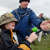 "Micah Oren, 9, left, reels in the first catch of the day with the help of his father Bret during the Fishing Derby sponsored by the Colorado Division of Wildlife and Broomfield Open Space Foundation at Tom Frost Reservoir on Saturday. Micah Oren nicknamed the fish "" Big Willy"".<br /> May 14, 2010<br /> Staff photo/ David R. Jennings"