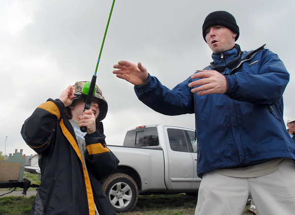 Micah Oren, 9, left, reels in the first catch of the day with the help of his father Bret during the Fishing Derby sponsored by the Colorado Division of Wildlife and Broomfield Open Space Foundation at Tom Frost Reservoir on Saturday.<br /> May 14, 2010<br /> Staff photo/ David R. Jennings