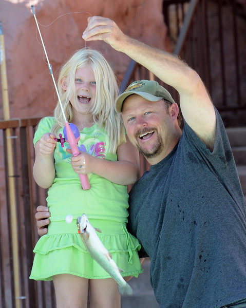 Kaitlyn Baker, 7, and her father Tim pose for pictures with a Rainbow Trout they caught while fishing during Fishing at the Bay on Saturday.<br /> <br /> September 25, 2010<br /> staff photo/David R. Jennings