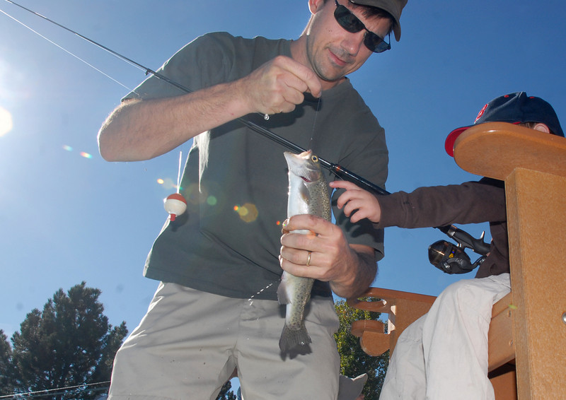 Mike Artmann holds a Rainbow Trout for his son Ryan, 3, during Fishing at the Bay on Saturday.<br /> <br /> September 25, 2010<br /> staff photo/David R. Jennings