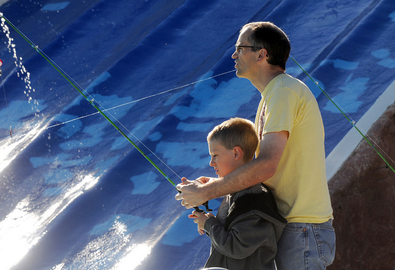 Mason Scoggin, 9, is helped by his father Chris while fishing during Fishing at the Bay on Saturday.<br /> <br /> September 25, 2010<br /> staff photo/David R. Jennings