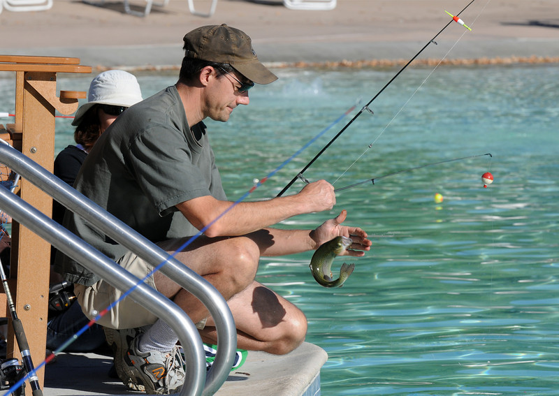 Mike Artmann reels in a Rainbow Trout for his sons while fishing with his family during Fishing at the Bay on Saturday.<br /> <br /> September 25, 2010<br /> staff photo/David R. Jennings