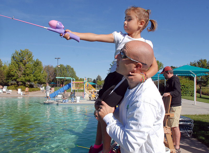 Dave Delier holds his daughter Payton, 5, on his shoulder so she can get better distance while castig during Fishing at the Bay on Saturday.<br /> <br /> September 25, 2010<br /> staff photo/David R. Jennings