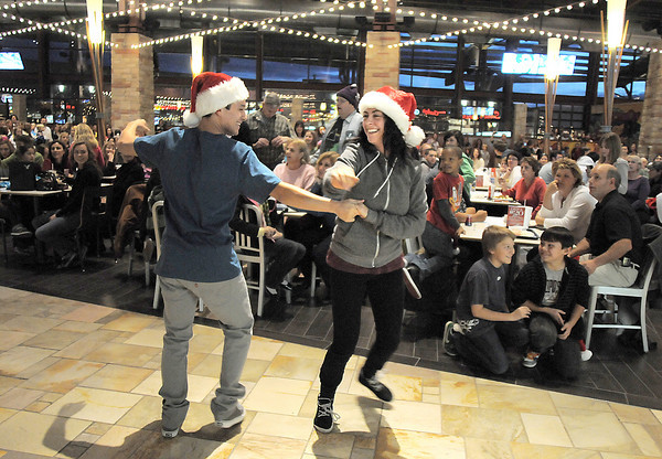 """Hannah Vincent and Mikey Ruiz with Break EFX  lead a flash mob of over 200 people dancing to Mariah Carey's song """"All I want for Christmas is you"""" surrounding shoppers in the food court of FlatIron Crossing mall on Thursday. Dancers from Artistic Fusion Dance Academy participated in the flash mob.<br /> December  9, 2010<br /> staff photo/David R. Jennings"""
