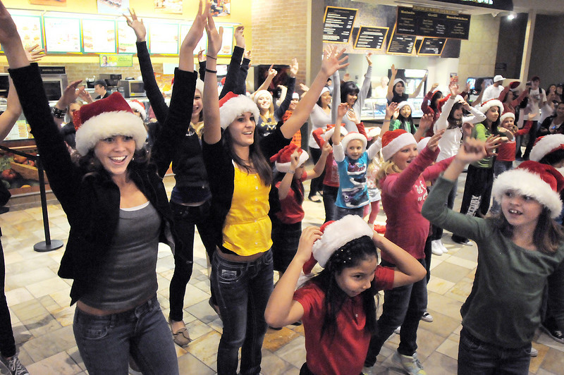 """Ashley Sullivan, 17, left, and Brooke Jones, 16, dancers with Artistic Fusion Dance Academy, helped lead a flash mob of over 200 people dancing to Mariah Carey's song """"All I want for Christmas is you"""" surrounding shoppers in the food court of FlatIron Crossing mall on Thursday. <br /> December  9, 2010<br /> staff photo/David R. Jennings"""