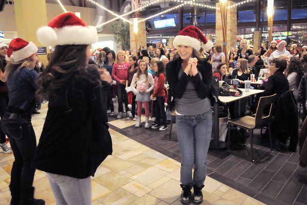 "Ashley Sullivan, 16, center, and fellow Artistic Fusion Dance Academy dancers perform as other dancers wait to begin dancing in a flash mob of over 200 people dancing to Mariah Carey's song ""All I want for Christmas is you"" surrounding shoppers in the food court of FlatIron Crossing mall on Thursday. Dancers from Break EFX participated in the flash mob.<br /> December  9, 2010<br /> staff photo/David R. Jennings"
