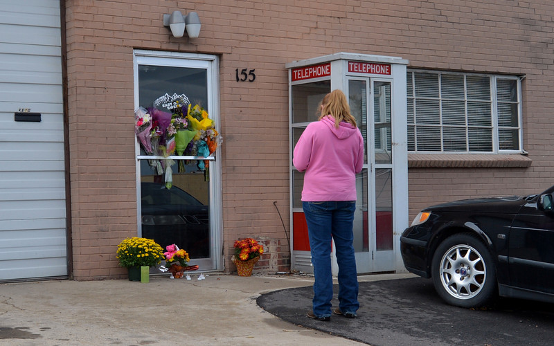 A woman looks at the flowers placed at the front door of East of Sweden in memory of Mary McGrath, an employee of the Saab repair shop, was shot a killed on Friday.<br /> October 13, 2012<br /> staff photo/ David R. Jennings