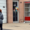 An East of Sweden customer, who wished not to be identified, walks to place flowers at the front door of the business in memory of Mary McGrath, an employee of the Saab repair shop, was shot a killed on Friday.<br /> October 12, 2012<br /> staff photo/ David R. Jennings