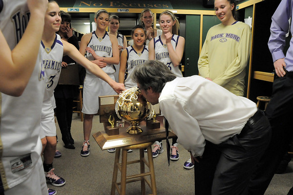 Holy Family's coach Ron Rossi kisses the 3A state championship trophy in the locker room as the team watches after they defeated Eaton in Saturdays game at Moby Arena in Ft. Collins.<br /> March 12, 2011<br />  staff photo/David R. Jennings