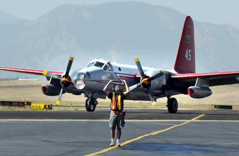 Parking tender Mark VonAllman directs an airtanker as another taxies into the US Forest Service Airtanker base at Rocky Mountain Metro Airport while fighting the Four Mile Fire in Boulder County on Tuesday. <br /> <br /> September 7, 2010<br /> staff photo/David R. Jennings