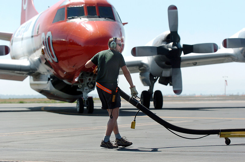 Retardant loading crew member Will Leininger, US Forest Service Airtanker base at Rocky Mountain Metro Airport,  moves the filler hose away from an airtanker after filling the aircraft with fire retardant as another airtanker waits to be loaded to fight the Four Mile Canyon Fire in Boulder County on Tuesday. <br /> <br /> September 7, 2010<br /> staff photo/David R. Jennings