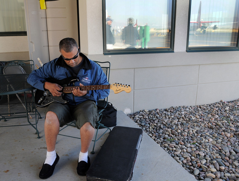 Michael Huston, crew chief for P-3 number 21, plays the guitar at the US Forest Service Airtanker base at Rocky Mountain Metro Airport  while waiting for the inversion over the Four Mile Canyon Fire to lift on Tuesday. <br /> September 7, 2010<br /> staff photo/David R. Jennings