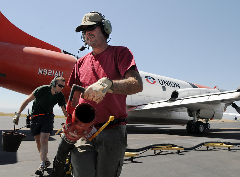 Retardant loading crew members Steve Wood and Will Leininger at the US Forest Service Airtanker base at Rocky Mountain Metro Airport move the filler hose away from a P-3 airtanker after filling the aircraft with fire retardant to fight the Four Mile Canyon Fire in Boulder County on Tuesday. <br /> September 7, 2010<br /> staff photo/David R. Jennings