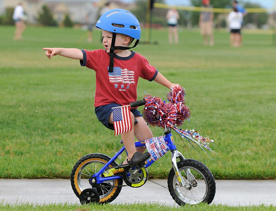 Derek Krug, 3 1/2, rides in the bike parade during Broomfield's Great American Picnic at County Commons Park.  July 4, 2009 staff photo/David Jennings