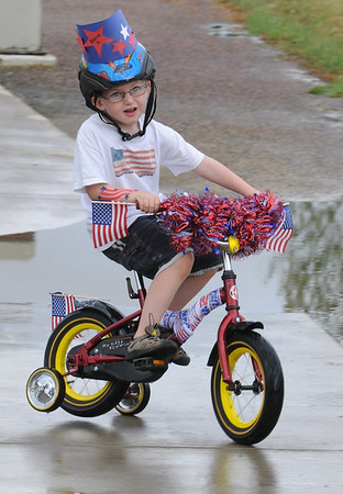 Blaine Krug, 4 1/2, rides around a puddle during the bike parade at Broomfield's Great American Picnic at County Commons Park.<br /> <br /> July 4, 2009<br /> staff photo/David Jennings