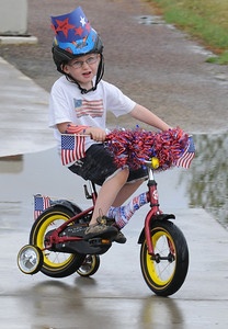 Blaine Krug, 4 1/2, rides around a puddle during the bike parade at Broomfield's Great American Picnic at County Commons Park.  July 4, 2009 staff photo/David Jennings