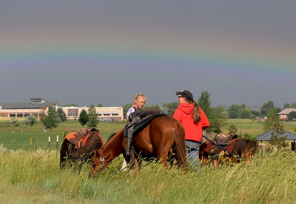 A rainbow enhances the view for Anna Robertson, 15, right, and Ksenis Bachina, 13, holding ponies for the Wild West Ranch pony rides during Broomfield's Great American Picnic at County Commons Park.<br /> <br /> July 4, 2009<br /> staff photo/David Jennings