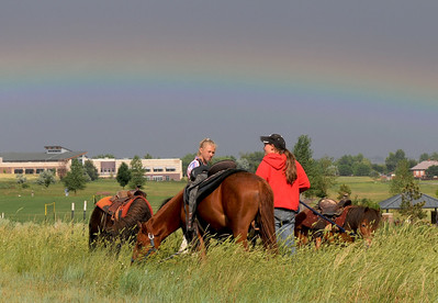 A rainbow enhances the view for Anna Robertson, 15, right, and Ksenis Bachina, 13, holding ponies for the Wild West Ranch pony rides during Broomfield's Great American Picnic at County Commons Park.  July 4, 2009 staff photo/David Jennings