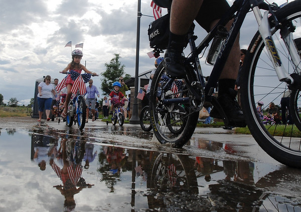 Bike parade participants ride through a puddle to start the parade during Broomfield's Great American Picnic at County Commons Park.<br /> <br /> July 4, 2009<br /> staff photo/David Jennings