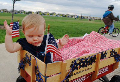 Maggie Scoles, 1, rides in a wagon during  the bike parade at Broomfield's Great American Picnic at County Commons Park.  July 4, 2009 staff photo/David Jennings
