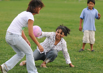 Silvia Acevedo, center tries to tag out her daughter Nezly, 16, as her son Jesus, 8, watches during an improvised game of baseball during Broomfield's Great American Picnic at County Commons Park.  July 4, 2009 staff photo/David Jennings