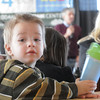 Nicholas Jezierski, 2, keeps his drink in hand while Frank Shorter talks in the background during the kick-off conference for the Frank Shorter's Race 4 Kids' Health fundraiser for Healthy Learning Paths at the 1st BankCenter on Thursday.<br /> February 2, 2012<br /> staff photo/ David R. Jennings
