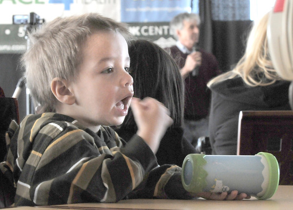 Nicholas Jezierski, 2, eats while  while Frank Shorter talks in the background during the kick-off conference for the Frank Shorter's Race 4 Kids' Health fundraiser for Healthy Learning Paths at the 1st BankCenter on Thursday.<br /> February 2, 2012<br /> staff photo/ David R. Jennings