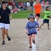 Jacinta Win, 16, left, with the Springwood Stingers from Brisbane Australia runs with Michaela Woods, 8, to home during the Adopt-A-Team Program game to start the Colorado Freedom Invitational Softball Tournament at the Community Park ballfields on Friday.<br /> <br /> June 29, 2012<br /> staff photo/ David R. Jennings