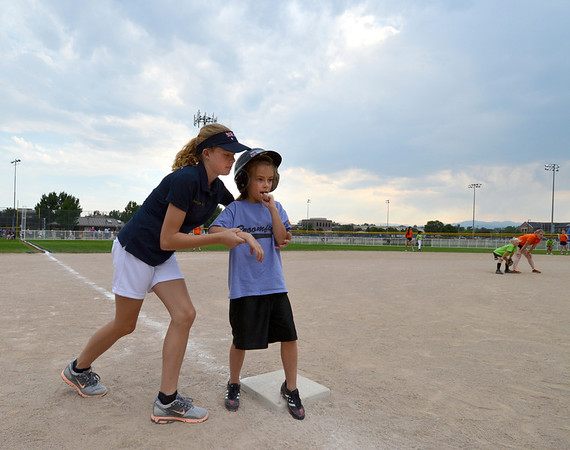"""Kylie Thomas, 13, left, with the Springwood Stingers from Brisbane Australia gives some pointers to Riley O'Malley, 7, on preparing to run to home plate during the Adopt-A-Team Program game to start the Colorado Freedom Invitational Softball Tournament at the Community Park ballfields on Friday.<br /> <br /> June 29, 2012<br /> staff photo/ David R. Jennings<br /> <br /> for more photos please go to  <a href=""""http://www.broomfieldenterprise.com"""">http://www.broomfieldenterprise.com</a>"""