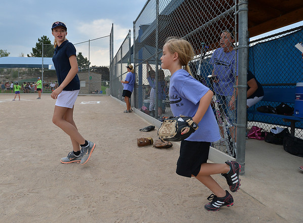 "Tianah List, 13, left,  with the Springwood Stingers from Brisbane Australia runs with Taylor Melssen, 7, to the field during the Adopt-A-Team Program game to start the Colorado Freedom Invitational Softball Tournament at the Community Park ballfields on Friday.<br /> <br /> June 29, 2012<br /> staff photo/ David R. Jennings<br /> <br /> for more photos please go to  <a href=""http://www.broomfieldenterprise.com"">http://www.broomfieldenterprise.com</a>"