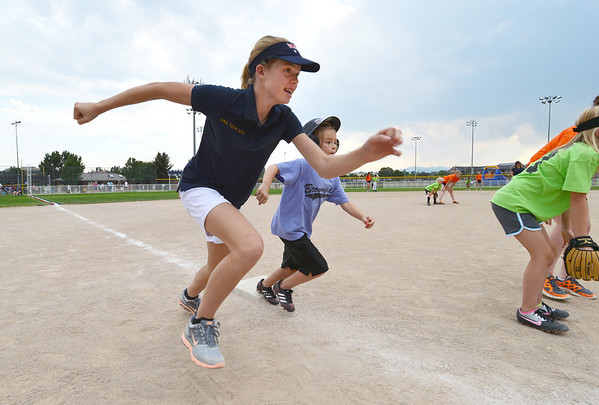 "Kylie Thomas, 13, left, with the Springwood Stingers from Brisbane Australia runs to home plate with Riley O'Malley, 7, during the Adopt-A-Team Program game to start the Colorado Freedom Invitational Softball Tournament at the Community Park ballfields on Friday.<br /> <br /> June 29, 2012<br /> staff photo/ David R. Jennings<br /> <br /> for more photos please go to  <a href=""http://www.broomfieldenterprise.com"">http://www.broomfieldenterprise.com</a>"