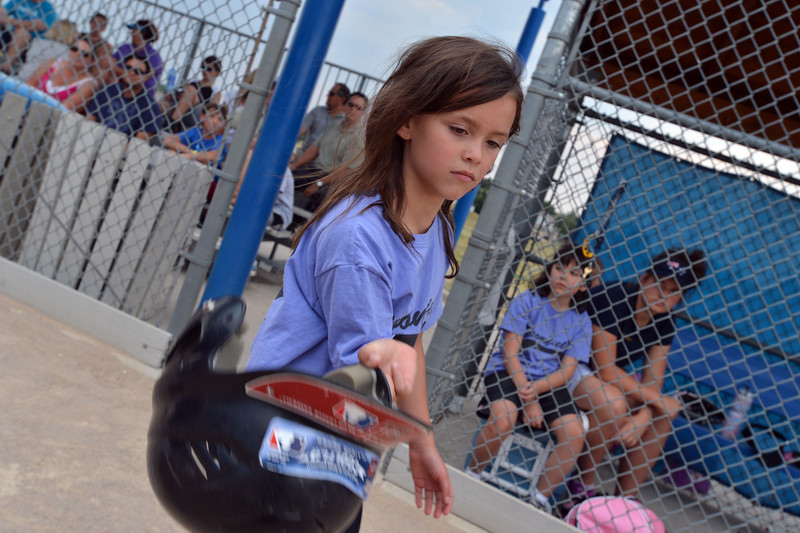 "Dirt Divas player Riley O'Malley, 7,removes her batting helmet at the end of an inning during the Adopt-A-Team Program game to start the Colorado Freedom Invitational Softball Tournament at the Community Park ballfields on Friday.<br /> <br /> June 29, 2012<br /> staff photo/ David R. Jennings<br /> <br /> for more photos please go to  <a href=""http://www.broomfieldenterprise.com"">http://www.broomfieldenterprise.com</a>"