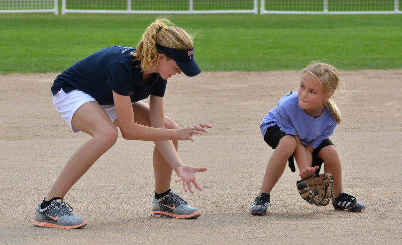 """Tianah List, 13, left, with the Springwood Stingers from Brisbane Australia gives fielding a ball to Taylor Melssen, 7, during the Adopt-A-Team Program game to start the Colorado Freedom Invitational Softball Tournament at the Community Park ballfields on Friday.<br /> <br /> June 29, 2012<br /> staff photo/ David R. Jennings<br /> <br /> for more photos please go to  <a href=""""http://www.broomfieldenterprise.com"""">http://www.broomfieldenterprise.com</a>"""