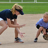 "Tianah List, 13, left, with the Springwood Stingers from Brisbane Australia gives fielding a ball to Taylor Melssen, 7, during the Adopt-A-Team Program game to start the Colorado Freedom Invitational Softball Tournament at the Community Park ballfields on Friday.<br /> <br /> June 29, 2012<br /> staff photo/ David R. Jennings<br /> <br /> for more photos please go to  <a href=""http://www.broomfieldenterprise.com"">http://www.broomfieldenterprise.com</a>"