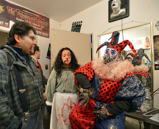 Frightmare Compound actors Marco Fernandez, left, and  his brother Rodrigo Fernandez with Angelica Garces, center, prepare for their parts in the green room before the haunted house  opens on Friday night.<br /> October 5, 2012<br /> staff photo/ David R. Jennings