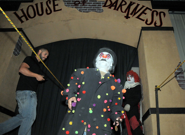 Clown Little Lonie stands at the entrance of the House of Darkness to let visitors in while owner Josh Holder, left, makes sure everything is ready at the Frightmare house at 108th and Olde Wadsworth on Saturday.<br /> October 15, 2011<br /> staff photo/ David R. Jennings