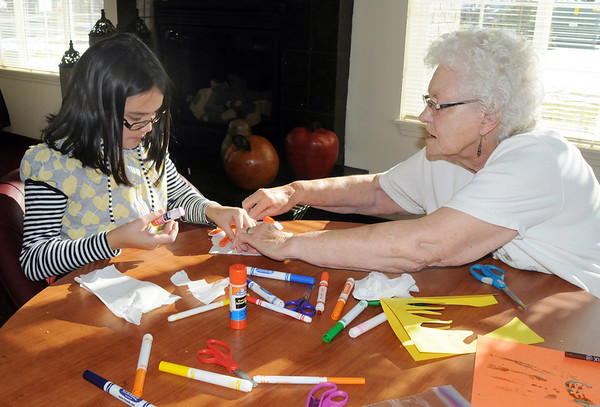 Coyote Ridge Elementay School 4th grader, Danielle Dean, left, and Thelma Worker help each other make a Thanksgiving centerpiece for the residents of  Highland Trail Highland Trail independent-living retirement community on Friday. <br /> November 20, 2009<br /> Staff photo/David R. Jennings