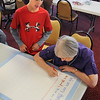 Coyote Ridge Elementay School 4th grader, Reilly Lavelle, left, watches resident Mary Anderson fill out a Thanksgiving poster for the residents of Highland Trial assisted living community on Friday. <br /> November 20, 2009<br /> Staff photo/David R. Jennings
